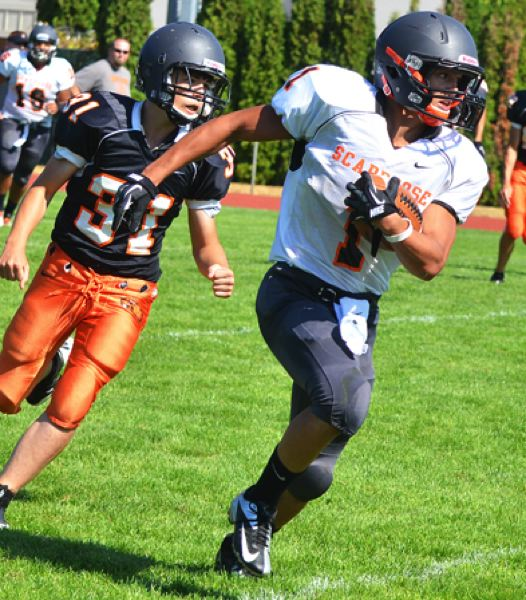 by: JOHN BREWINGTON - Carson Davison carries the ball for big yards during last Saturday's scrimmage in Scappoose. Davidson is expected to see a good deal of action this Friday when Scappoose hosts Roosevelt in the first game of the season.