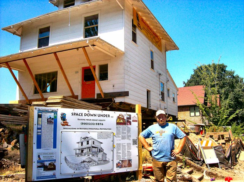 by: RITA A. LEONARD - Michael Musumeci, owner of Space Down Under LLC construction, with the century-old home he is moving away from the cliff on the lot, and with the display board describing the project.
