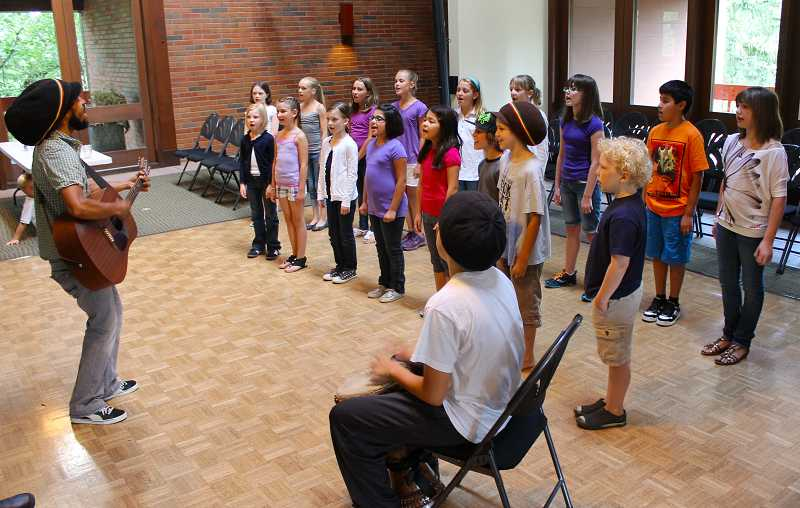 by: SUBMITTED - Children in the Portland-based choir, including kids from both West Linn and Lake Oswego, rehearse for the One World Children's Chorus. They are led by Aaron Nigel Smith on guitar.