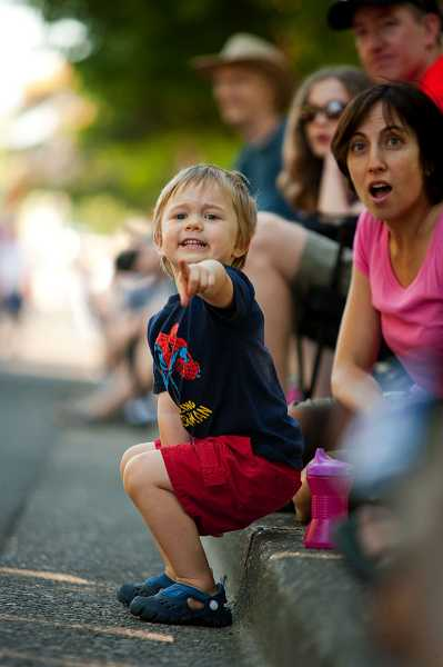 by: CHRISTOPHER ONSTOTT - Lorenzo Freddi, 3, and his mother, Marcy, can hardly contain their excitement as the Beaverton motorcycle police race down the street in the 2011 Celebration Parade.