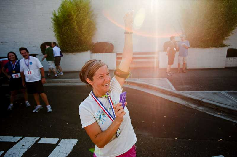 by: CHRISTOPHER ONSTOTT - Jessica McCurdy cheers on a friend at the finish line of the inaugural Family Fun Run.