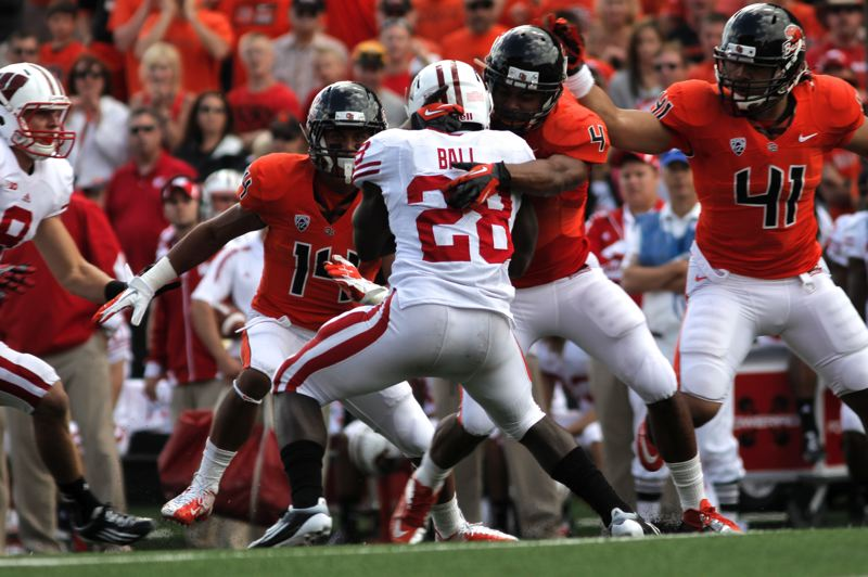 by: TRIBUNE PHOTO: JAIME VALDEZ - Oregon State linebacker D.J.Welch upends Wisconsin Badgers running back Montee Ball as other Beavers defenders close in on the play.