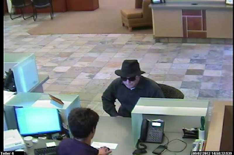 by: SUBMITTED - Security cameras caught a photo of a man in a fedora who allegedly robbed the MBank branch on McEwan Avenue near Lake Oswego.
