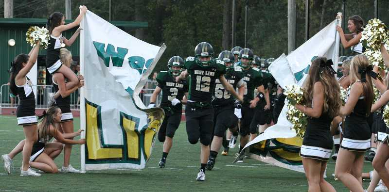 by: J. BRIAN MONIHAN - The West Linn High School Lions make their appearance for the game against Grants Pass Sept. 7.