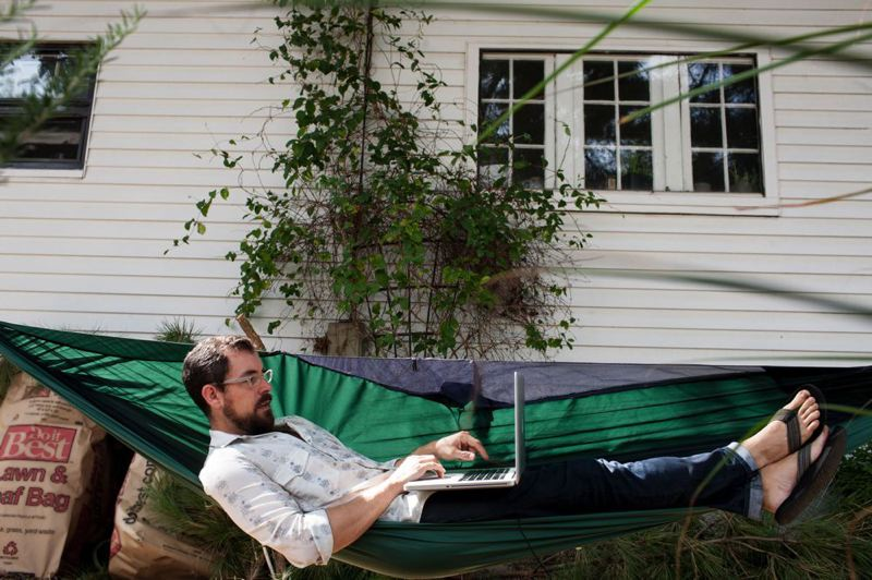 by: TRIBUNE PHOTO: CHRISTOPHER ONSTOTT - Engineer Evan Jones (top) relaxes while getting some computer work done in his yard, practicing what he calls 'pretirement.' He wonders if Portland's young creatives have lost, or redefined, ambition.