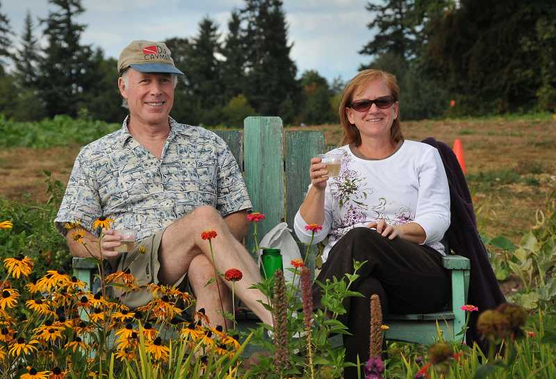 by: VERN UYETAKE - Steve  and Mindy Todd relax with glasses of wine after some hard work weeding their garden plot and harvesting tomatoes at Luscher Farm.