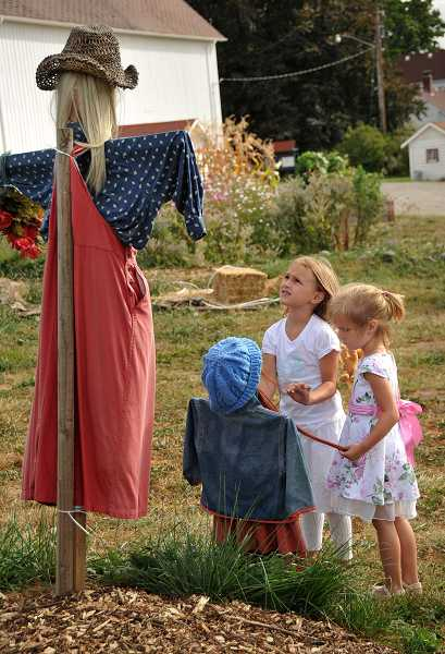 by: VERN UYETAKE - Amandia, 5, and Julieta, 3, Scotti check out all the scarecrows protecting the garden at Luscher Farm.