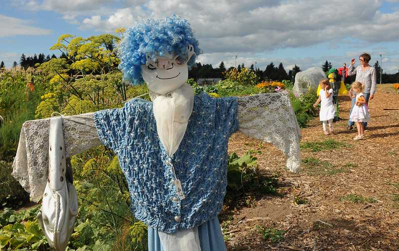 by: VERN UYETAKE - The garden is filled with many creatively decorated scarecrows.