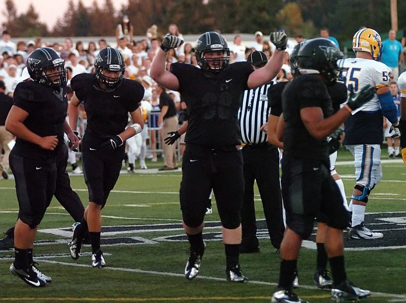 by: DAN BROOD - TIGER BALL - Tigard High School senior lineman Blake Chamberlain puts his arms in the air after Tiger junior defensive end A.J. Hotchkins recovered an Aloha fumble in Friday's contest.