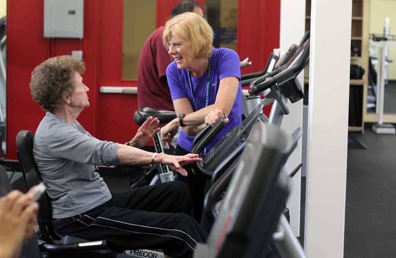by: JONATHAN HOUSE - Personal trainer Carol Kirgger chats with Dolores Bowman in the Garden Home Recreation Center's new fitness room. The center will be having an open house this Saturday to show off the new equipment and offerings.