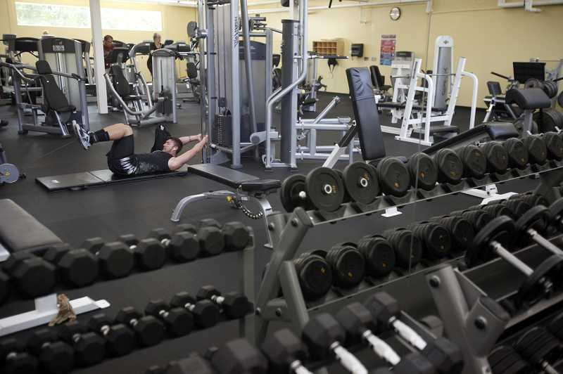 by: JONATHAN HOUSE - Weights and new fitness machines adorn the new workout room at the Garden Home Recreation Center.