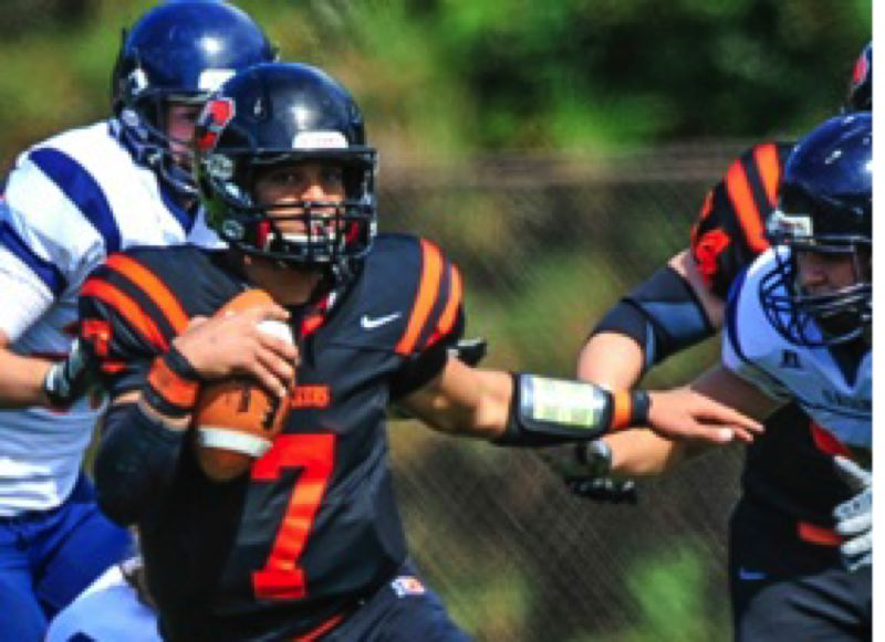 by: MICHAEL WORKMAN - Quarterback Keith Welch evades the Pomona-Pitzer defense as the Lewis & Clark Pioneers win their home opener 31-13 Saturday at Griswold Stadium.
