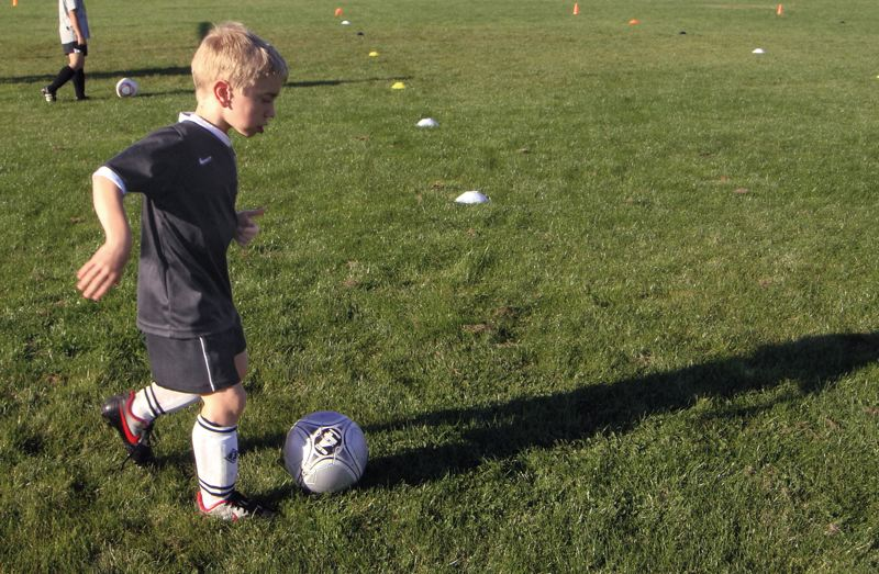 by: SUBMITTED PHOTO - Adin Williams moves the ball around as he get ready for a soccer game with Clackamas United.
