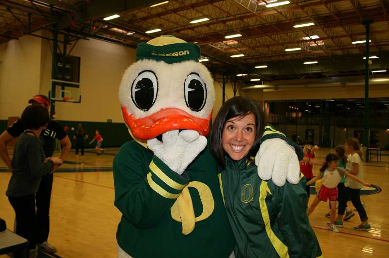 by: SUBMITTED PHOTO - The Oregon Duck gives a big hug of congratulations to MindyLockard, who seems overwhelmed but happy after she gave a seminar on gracious behavior to 47 University of Oregon cheerleaders.
