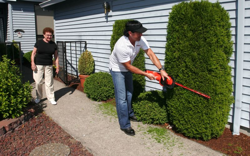 by: JIM CLARK - GruntWorks contractor John Baringa trims a hedge for Summerplace resident Thelma Erlendson.
