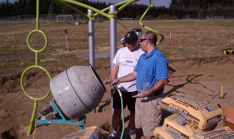 by: JENNIFER BUTTS - Volunteer Matt Butts, left, and Athey Creek Middle School Principal Joel Sebastian mix concrete for the new playground and fitness structure.