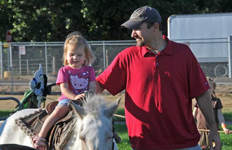 by: VERN UYETAKE  - Luke Foster and his daughter, Molly Rose Foster, 2, have fun on the pony rides.