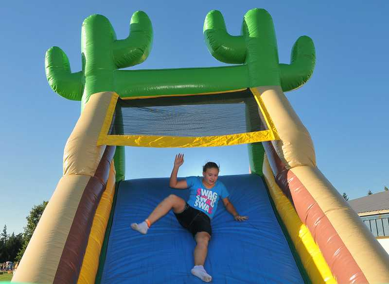by: VERN UYETAKE  - Sixth-grader Delaney Dougherty goes down the large inflatable slide.