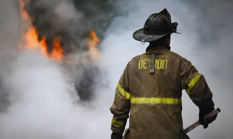 by: SUBMITTED - A Detroit firefighter heads toward the flames. On Putnam's first night of filming, the fire department faced 10 fires.