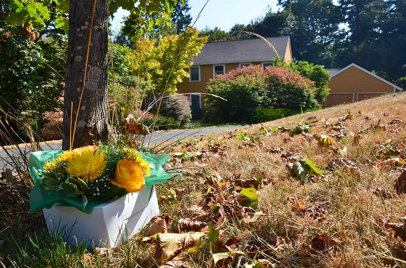by: VERN UYETAKE - Flowers sit across from the home of the Hayes family on Tuesday. Frederick 'Fritz' Wheeler Hayes Jr. died after being attacked by an intruder Monday morning.