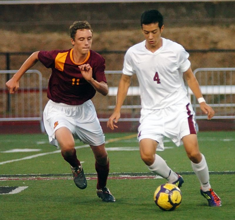 by: DAN BROOD - TURF WAR -- Tualatin senior Jonathan Thayer (right) battles Central Catholic junior Peter Bergmann for the ball.
