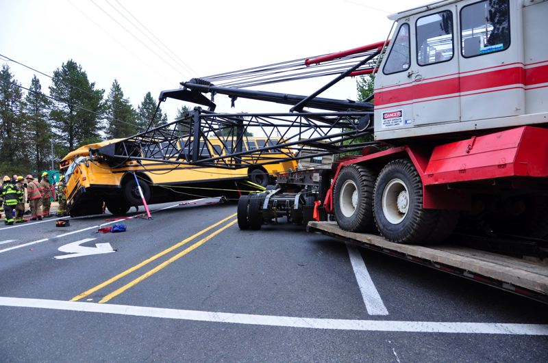by: COURTESY OF HILLSBORO FIRE DEPARTMENT - A Hillsboro school bus driver was injured Thursday morning when the tip of a construction crane slammed into the driver's side of his bus. No children were on the bus when the accident happened on Northwest Glencoe Road.