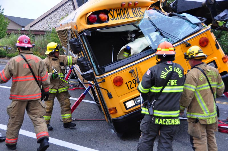 by: COURTESY OF HILLSBORO FIRE DEPARTMENT - Hillsboro firefighters had to remove the school bus doors to lift the injured driver out. The driver's injuries were not life-threatening, firefighters said.