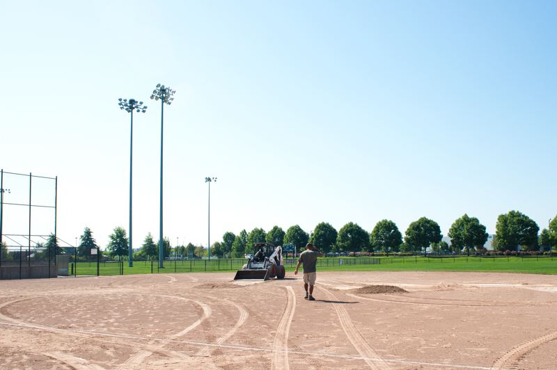 by: HILLSBORO TRIBUNE PHOTO: CHASE ALLGOOD - Hillsboro Parks & Recreation Ivan Pineda scrapes up the infield material from the softball field that is being replaced with the new baseball stadium. The infield material will be used at another Hillsboro park to save money.