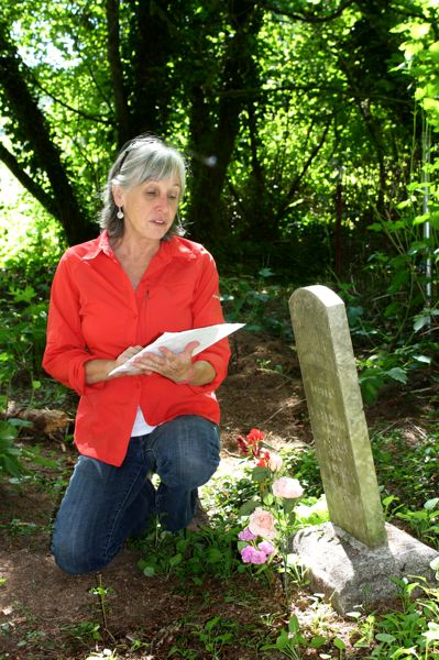 by: POST PHOTO: LISA K. ANDERSON  - Sally Donovan, a historic preservationist, explains headstone cleaning to volunteers at Cherryville Cemetery.