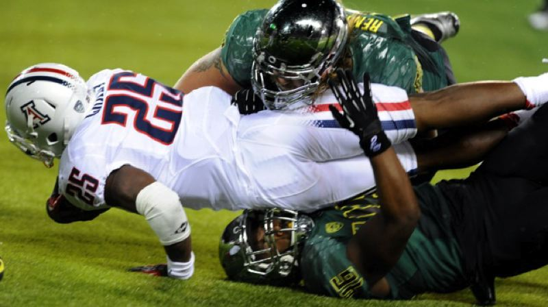 by: GREG WAHL-STEPHENS - Oregon's defense makes a stop on the way to a 49-0 win over Arizona.