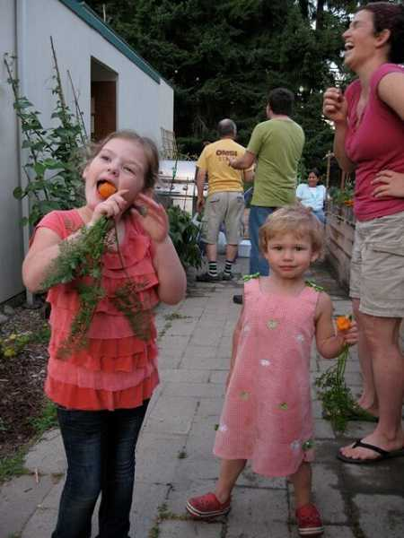 by: SUBMITTED - Kids enjoy the fruits of their labor at the Robinwood community garden by chomping down on fresh carrots.