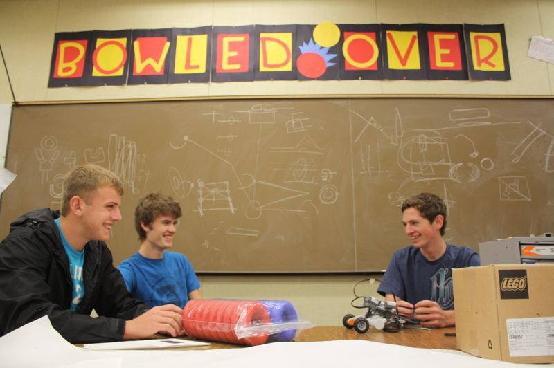 by: KATIE WILSON - St. Helens High School seniors, from left, Charlie Pense, Duncan Adams and Josh Hamilton brainstorm ideas in the classroom set aside for the robotics teams. The teams have done well in competition over the last three years. Educators and parents say the class and the tournaments expose students to other careers and possibilities.