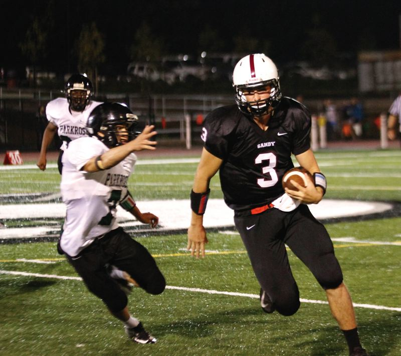 by: JULI CHURCHILL - Sandy quarterback Justin Adams rushed for two touchdowns, including one of 45 yards, in a 14-6 win over Parkrose on Friday at Sandy High School.