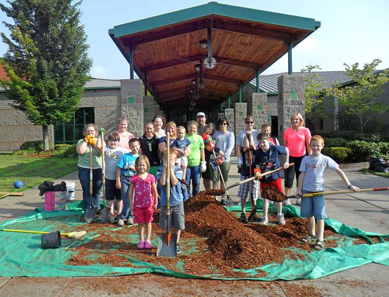 by: BARBARA SHERMAN - GROUP WORK â€' A group of Archer Glen Elementary parents and students take a break in front of the school during one of their summer work parties that met to spruce up the grounds by weeding, pruning and spreading bark chips.