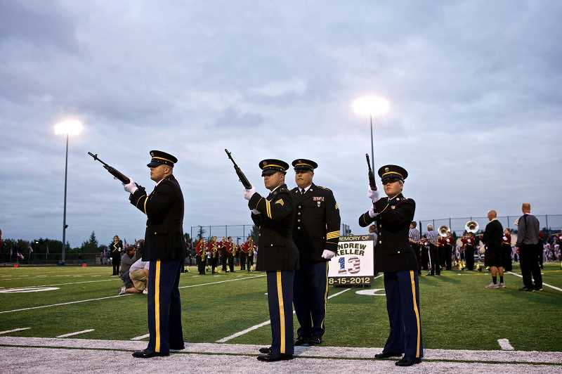 by: TIMES PHOTO: JAIME VALDEZ - The Jackson Armory Honor Guard led by Sgt. Brett Roesch fires their rifles to honor the service of U.S. Army Pfc. Andrew Keller before the Skyhawks football team faced off against the Lake Oswego Lakers. Keller was a 2008 graduate of Southridge High School.