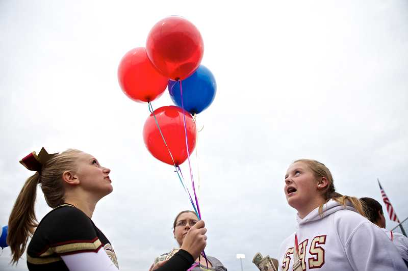 by: TIMES PHOTO: JAIME VALDEZ - Southridge Skyhawks sophomore cheerleader Meleah McGlinchy sells a balloon to freshman Mahaila Nieslanik. Proceeds from the balloon sales were donated to the Wounded Warrior Project in honor of Pfc. Andrew Keller. Friday night's balloon sales garnered more than $1,100 to help injured veterans.