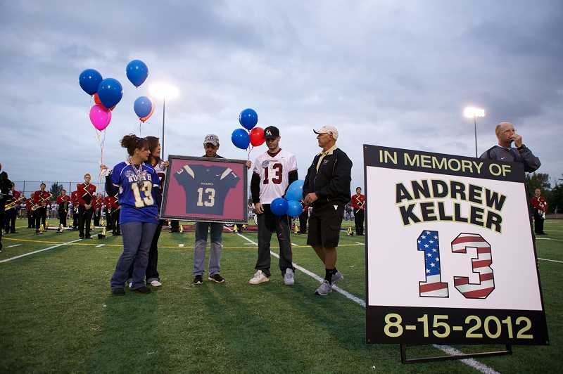 by: TIMES PHOTO: JAIME VALDEZ - Family members of U.S. Army Pfc. Andrew Keller, including his mother Kim, fiance Marissa Jones, father Jeff and brother Derek, pause for a moment after former Southridge High School football coach Brad Mastrud, right, presented them with a framed No. 13 football jersey.