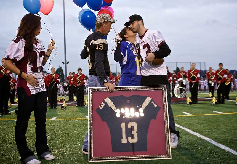 by: TIMES PHOTO: JAIME VALDEZ - Kim Keller kisses her 19-year-old son Derek after the No. 13 both he and his older brother Andrew wore was retired by Southridge High School on Friday night.