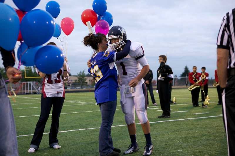 by: TIMES PHOTO: JAIME VALDEZ - Lake Oswego senior quarterback Ramey Harrison, No. 1, hugs Kim Keller, the mother of Pfc. Andrew Keller who was killed in action Aug. 15 while serving in Afghanistan.