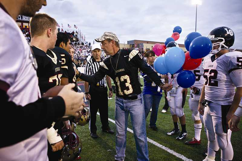 by: TIMES PHOTO: JAIME VALDEZ - Jeff Keller shakes hands with the captains of the Southridge Skyhawks and Lake Oswego Lakers football teams. Keller's eldest son Andrew served as captain of the Skyhawks during the 2007 football season. Andrew also was recognized by his teammates during his senior year as the Most Valuable Player.