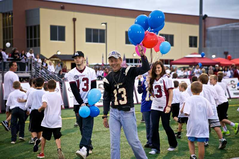 by: TIMES PHOTO: JAIME VALDEZ - Jeff Keller waves to the crowd at Southridge High School as his family steps onto the field for a special pre-game ceremony honoring his eldest son Pfc. Andrew Keller.