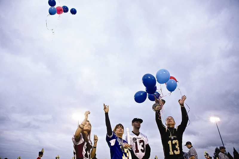 by: TIMES PHOTO: JAIME VALDEZ - Family members of U.S. Army Pfc. Andrew Keller, including his fiance Marissa Jones, mother Kim, brother Derek and father Jeff, release balloons into the sky as part of a colorful tribute to the 22-year-old Tigard soldier. Andrew Keller was killed in action Aug. 15 while serving in Afghanistan. The community gathered at Southridge High School's Friday night football game to pay tribute to the hometown hero.