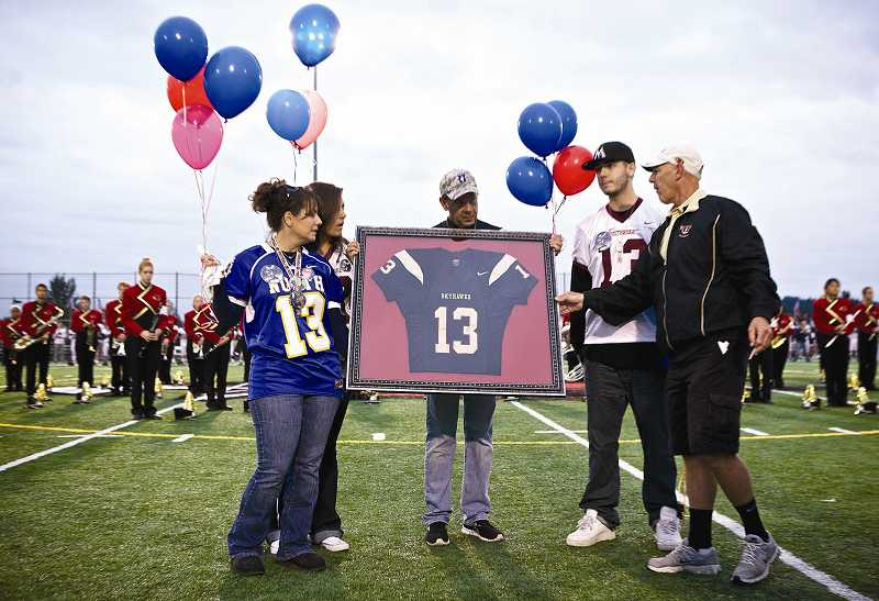 by: TIMES PHOTO: JAIME VALDEZ - Former Southridge High School football coach Brad Mastrud, right, presents the family of Pfc. Andrew Keller with a framed No. 13 football jersey. From left are his mother Kim, fiance Marissa Jones, father Jeff and younger brother Derek.