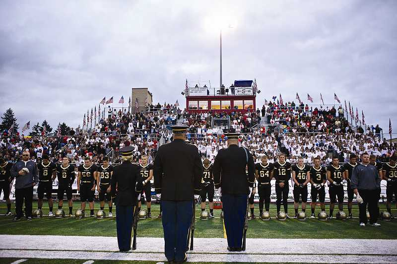 by: TIMES PHOTO: JAIME VALDEZ - The Jackson Armory Honor Guard led by Sgt. Brett Roesch fires a salute in honor of U.S. Army Pfc. Andrew Keller prior to the Friday night football game at his alma mater. Keller is a 2008 Southridge High School graduate.