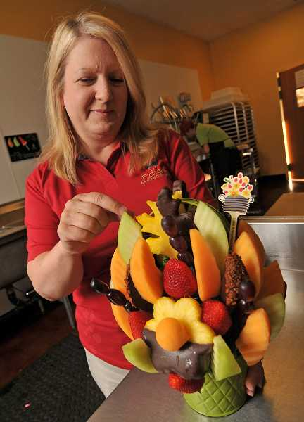 by: VERN UYETAKE - Cindy Craig arranges a fall Edible Arrangements basket with melons, strawberries, grapes and chocolate-covered strawberries.