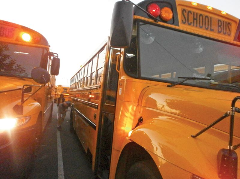 by: PHOTO BY NANCY TOWNSLEY/THE NEWS-TIMES - Hillsboro school bus drivers Ken Prickett and Bunny Bertsch perform pre-trip checks on their buses before leaving the parking lot in the early morning hours Sept. 17.