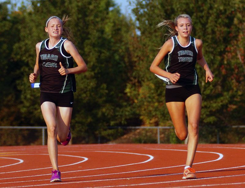 by: DAN BROOD - SIDE BY SIDE -- Tigard High School sophomores Hannaly Duff-McGaughey (left) and Elizabeth Dean are in the lead during last week's Pacific Conference dual meet with Glencoe. Both Tiger teams won.