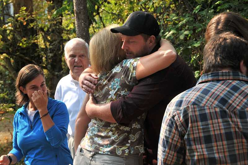 by: VERN UYETAKE - Ruth Hayes-Arista, whose brother was murdered last week in Lake Oswego, hugs Carl Kautz, the boyfriend of her niece Emily Hayes, left, on Monday. Also pictured is Frederick Hayes Sr., father of the late Fritz Hayes.