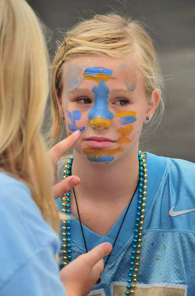by: REVIEW PHOTOS: VERN UYETAKE  - Racamie Boe, sixth grade, gets her face painted for the big game.