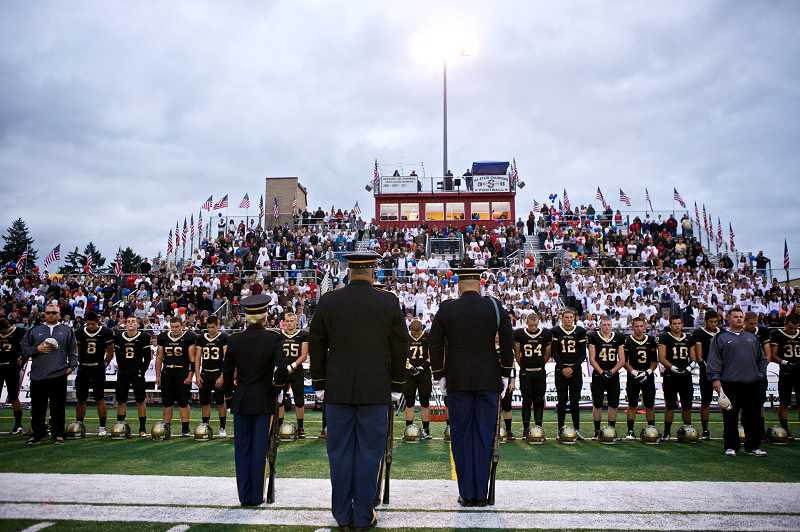 by: JAIME VALDEZ - The Jackson Armory Honor Guard led by Sgt. Brett Roesch fires a salute in honor of U.S. Army Pfc. Andrew Keller prior to the Friday night football game at his alma mater. Keller was a 2008 Southridge High School graduate.
